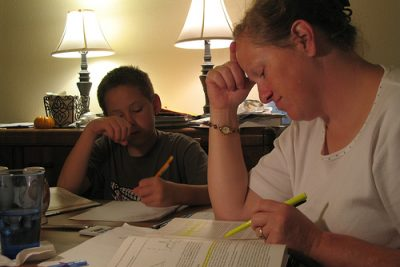 Woman and son, both doing homework on a table