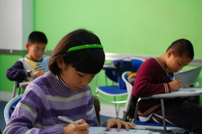 Three elementery kids sitting in school desks and taking a test
