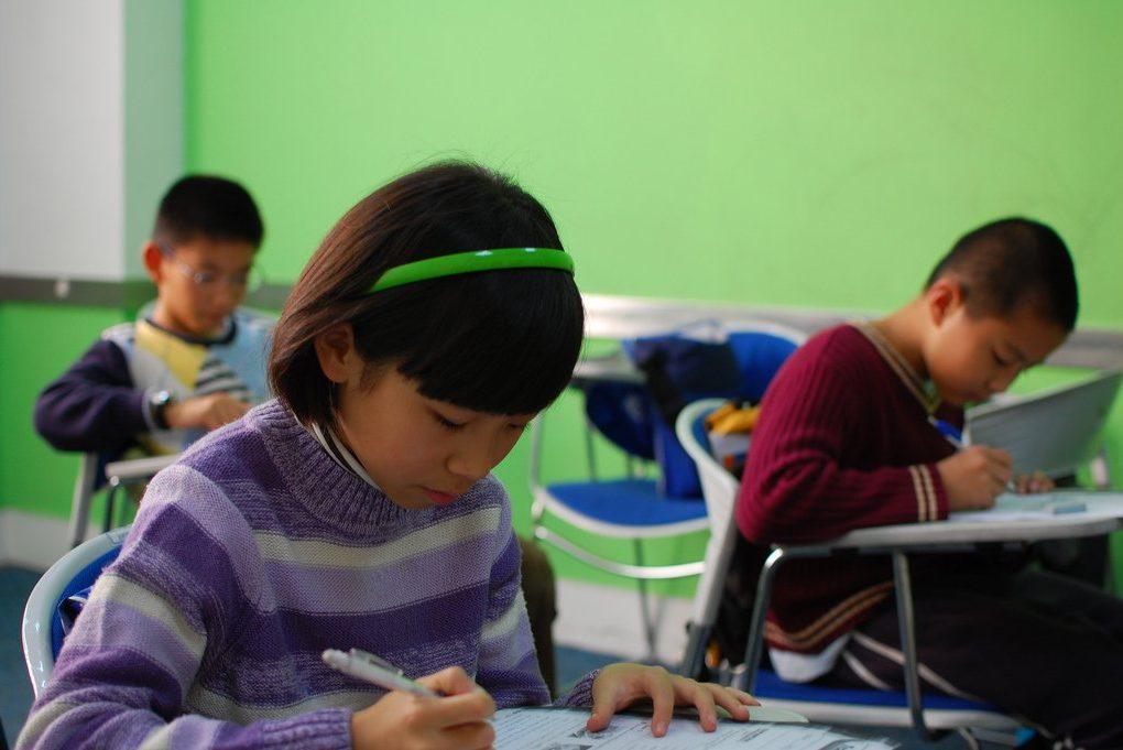 Three elementery kids sitting in school desks and taking a test