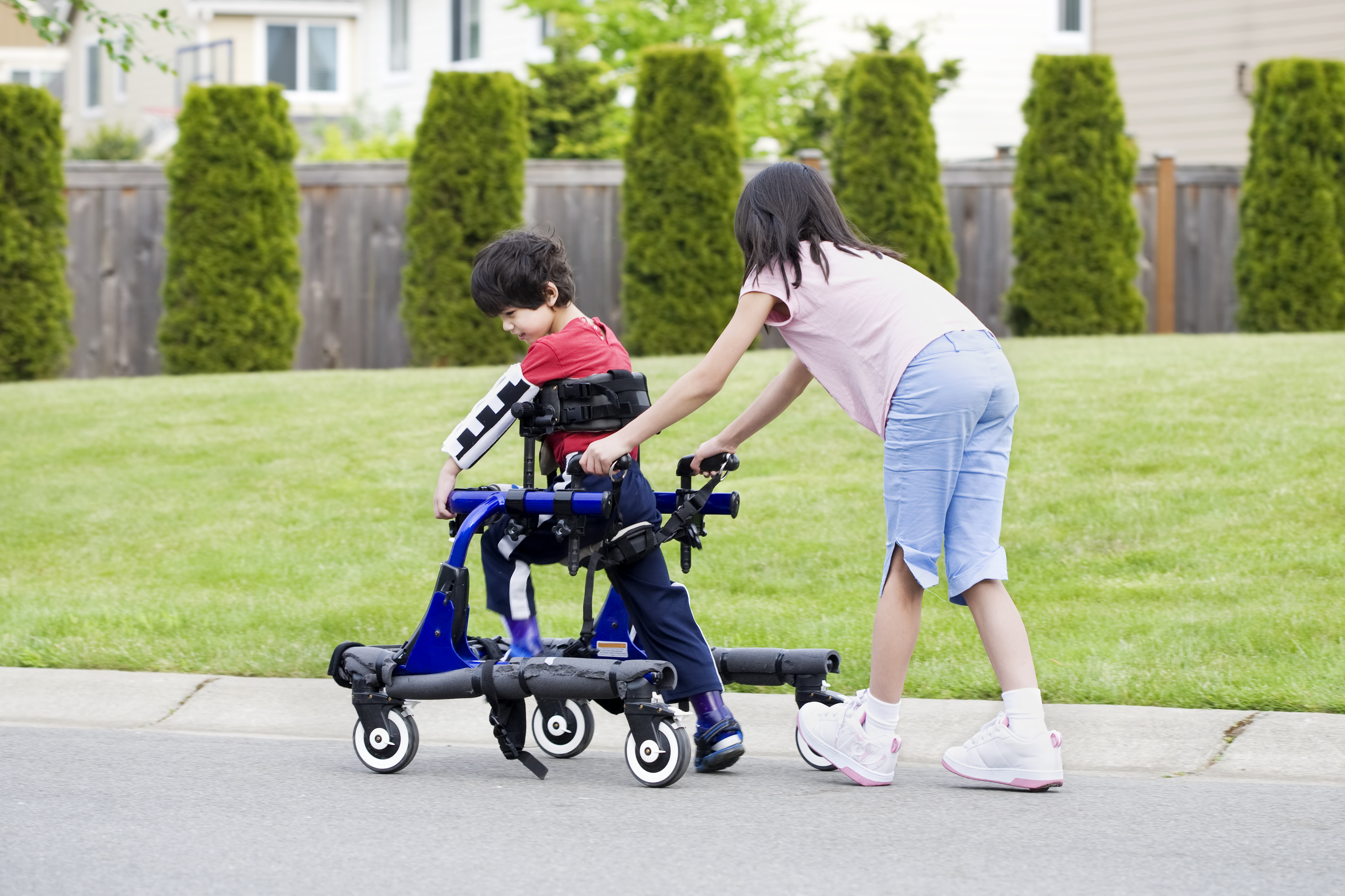Girl helping her younger brother walk in an apparatus