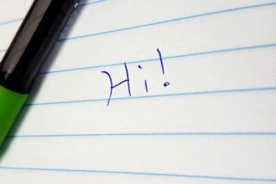"""Handwritten """"Hi"""" on a sheet of paper"""
