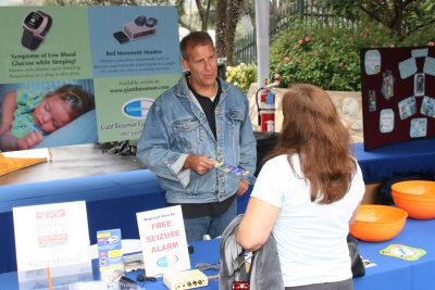 Man speaking to a woman at a informational stall