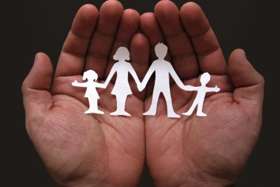 A pair of hands holding a cut out family