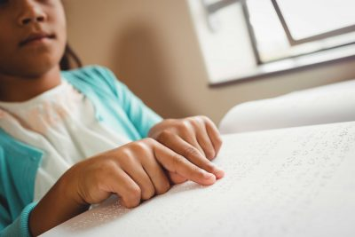 Girl using braille to read
