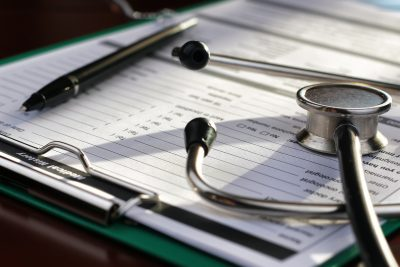 stethoscope, medical documents, and pen on a table