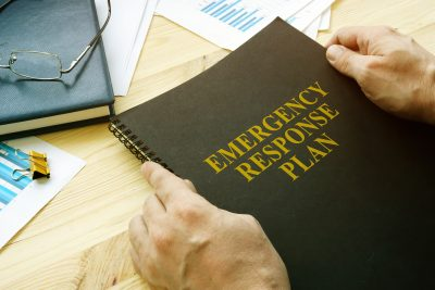 Man opening a disaster and emergency response plan for reading.