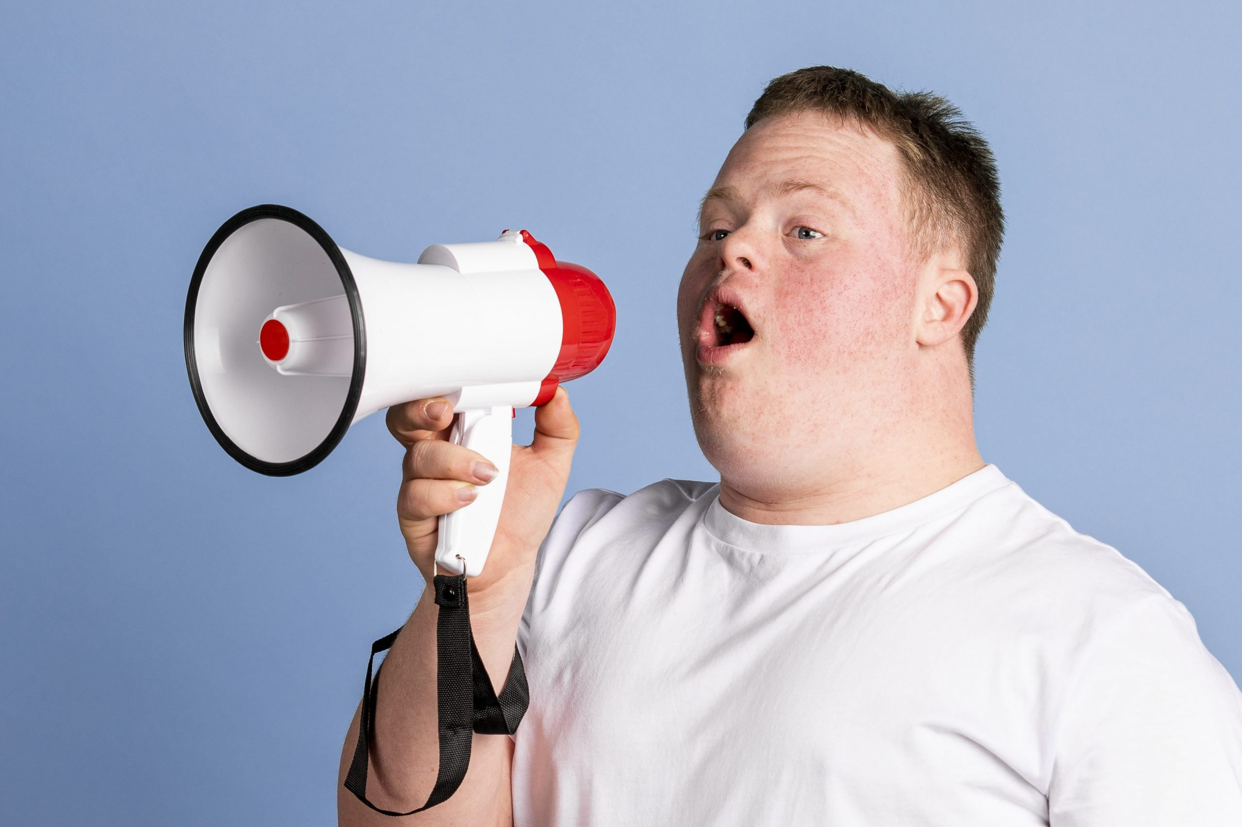Cute boy with down syndrome using a megaphone to amplify his voice