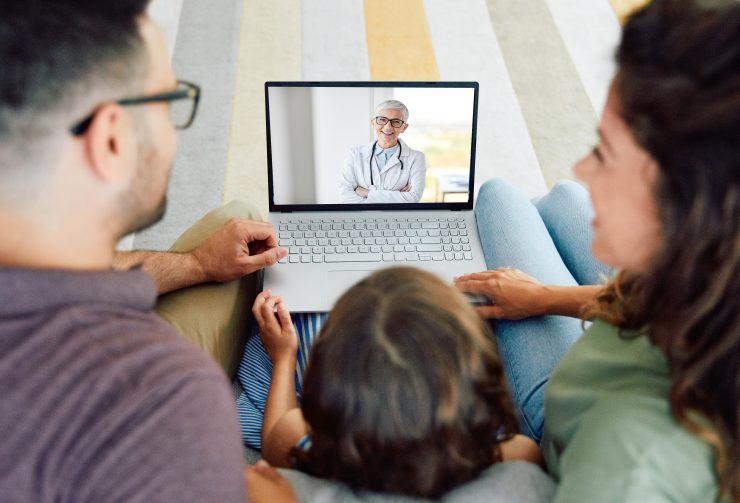Back view of family making video call with their doctor while staying at home