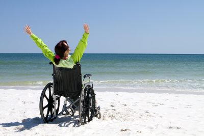 Woman with arms raised celebrates her achievement and success in the sunshine in a wheelchair.