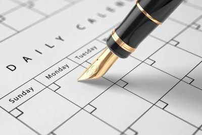 A luxury fountain pen writing in a calendar.
