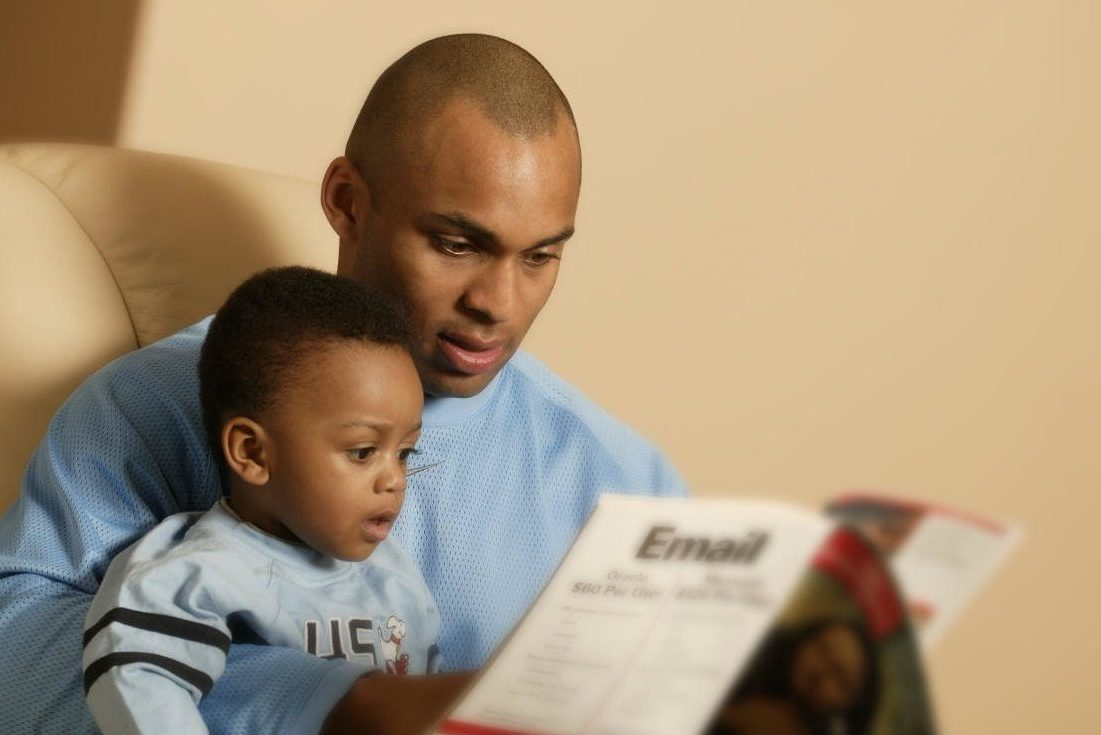 Father reading a book to his son