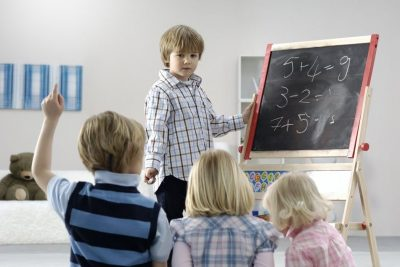 Young child at a blackboard teaching three other childeren