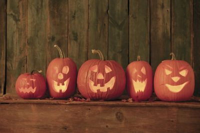 Five happy-faced Jack-o-lanterns in a row