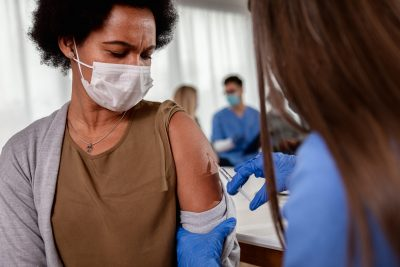 Female nurse with mask giving vaccine to patient in clinic.